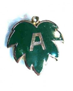 Green and silver enamel leaf-shaped pledge pin with silver letter A on it. Photo from Wikipedia, shared under Creative Commons licence.