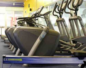 Photo showing a row of cross trainers and exercise bikes, by Flickr user sirwiseowl, shared under creative commons.