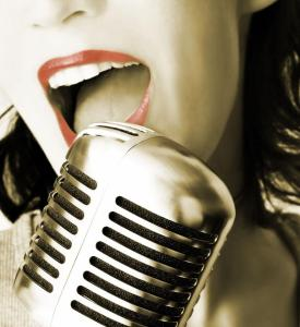 Image of a woman's mouth beind a microphone. Red lipstick and old-fashioned rockabilly mic