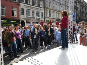 Hannah stood on a stage on cobbled stones performing to a large gathered crowd during the Edinburgh Fringe Festival
