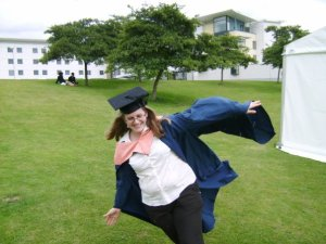 Hannah in graduation robes, arms out like an aeroplane, pretending to fly