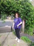 Hannah wearing her purple 'shine' marathon t-shirt, standing in front of some vines wearing trainers and black leggings