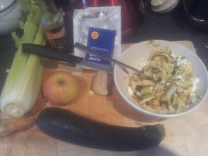 a bowl of courgette salad with the ingredients on a board